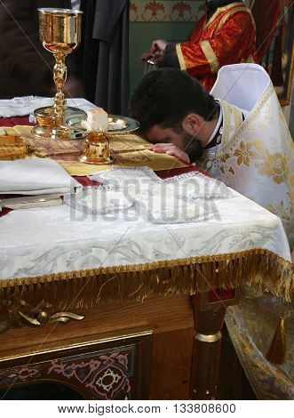 VOYUTYN UKRAINE - JANUARY 08 - Priest consecrates bread during orthodox liturgy ceremony in Voyutyn on January 08 2009.