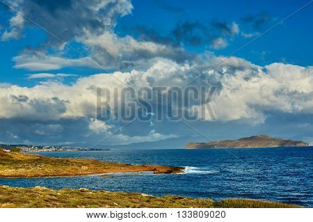 sunrise at the beach and beautiful dramatic sky with clouds in small bay. Chania city , Crete, Greece