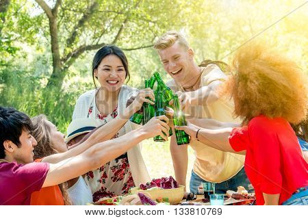 diverse friends at garden party saying cheers with bottles of beer - asian african and caucasian youth enjoying together