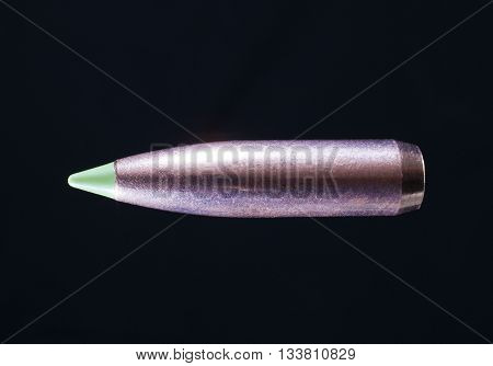 Bullet with a copper plating on polymer tip on a black background