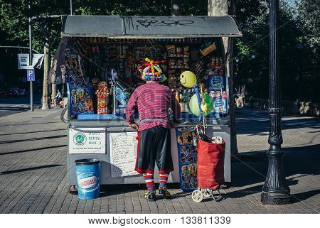 Barcelona Spain - May 22 2015. Man dressed as clown buys something at a kiosk in Barcelona city