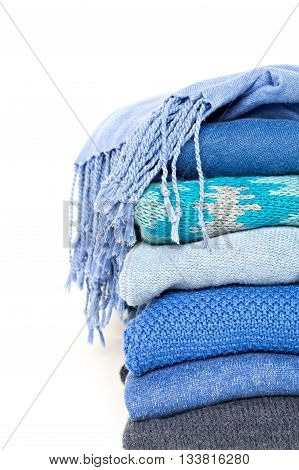stack of blue woolen knitted sweaters and shawl with a fringe isolated on white background