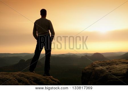 Silhouette of Young Confident and Powerful Man Standing with Hands on Hips Late Day Sun with Copy Space