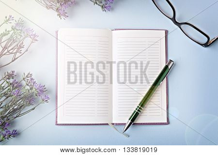 opened notebook with pen on blue table flat lay