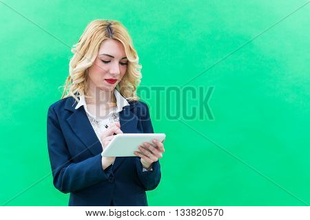 Young woman using tablet standing. Wearing blue suit she has blonde hair and blue or blue eyes on a white background. Smile always smiling.