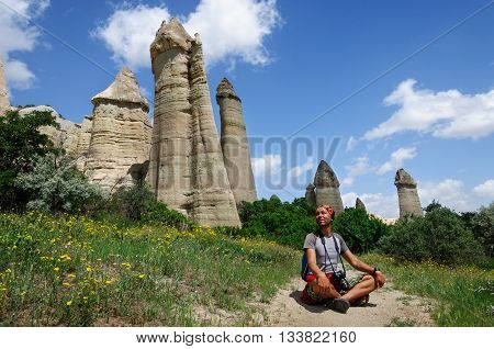 A young man sits on the edge of the canyon in Cappadocia. Turkey