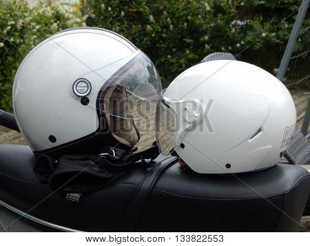 A kiss between two white bike helmets.