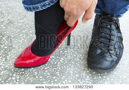 Man Putting On Red Ladies Shoes