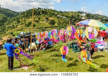 Sumpango Guatemala - November 1 2015: Kite vendor displays kites as visitors relax on hillside at giant kite festival on All Saints' Day honoring spirits of dead.