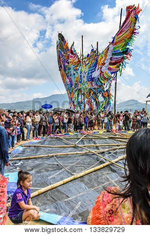 Sumpango Guatemala - November 1 2015: Visitors wait as team prepares to raise giant kite from ground at giant kite festival on All Saints' Day honoring spirits of dead.