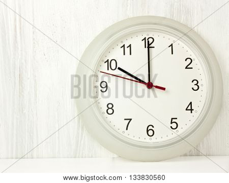 A photo of a typical office white clock with hands pointing at 10 o'clock on a pale wooden boards texture for copyspace; the beginning of the workday concept