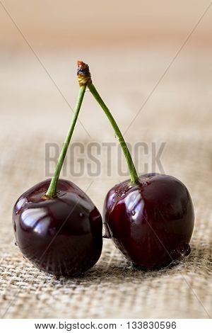two cherries with water drops on jute
