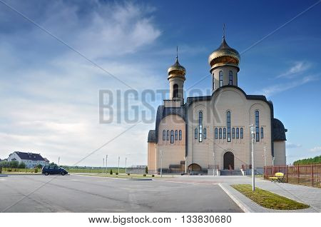 Grodno, Belarus - May 27, 2016: Modern Orthodox Church St. Seraphim of Sarov in the village Obukhovo Grodno region Belarus. Front facade with gold domes against the blue sky.