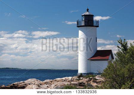 Annisquam Lighthouse over rocky harbor in Massachusetts.