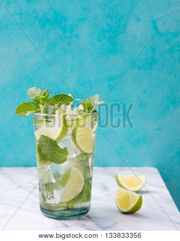 Mojito cocktail with lime and mint in highball glass on a marble table Blue background Copy space.