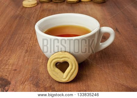 A white cup of tea with a butter cookie with a heart-shaped chocolate filling in the middle on a dark wooden texture with more blurred cookies in the background (can be cropped) with copyspace