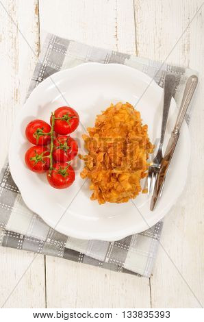 deep fried chicken fillet coated with corn flakes and wet tomato on a plate