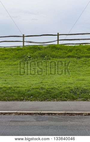 Five layers: Road Pedestrian pathway Grass field Wooden fence and Blue sky.