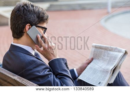 Businessman With Newspaper On Phone
