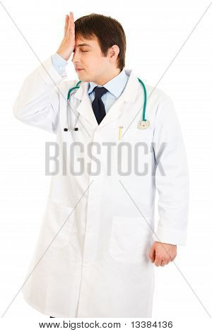 Forgot something medical doctor holding his hand near forehead isolated on white