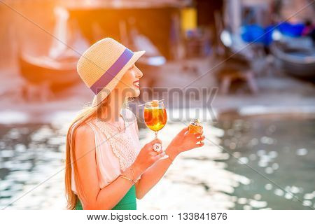 Young woman with glass of Spritz Aperol and italian snacks cicchetti sitting near the water chanal in Venice. Traditional venetian aperitif. Image with small depth of field