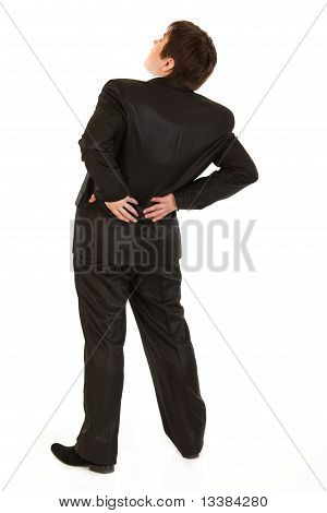 Businessman holding his hand at his aching back isolated on white
