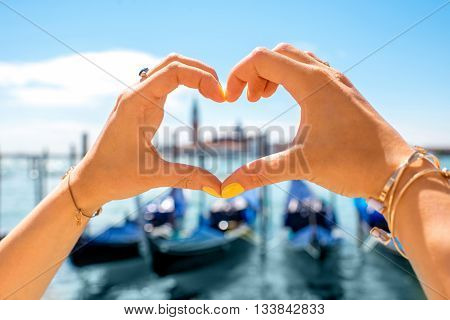 Heart shape made with hands with beautiful view on gondolas and San Giorgio Maggiore island in Venice. Love Venice city