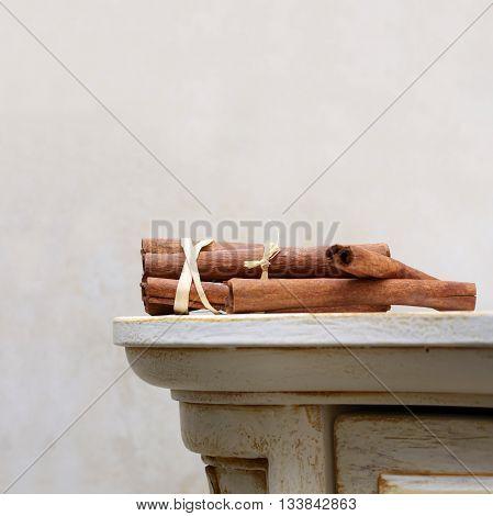 Brown cinnamon sticks lie on the vintage wooden desk