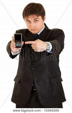 Confident businessman pointing finger on mobile with blank screen isolated on white