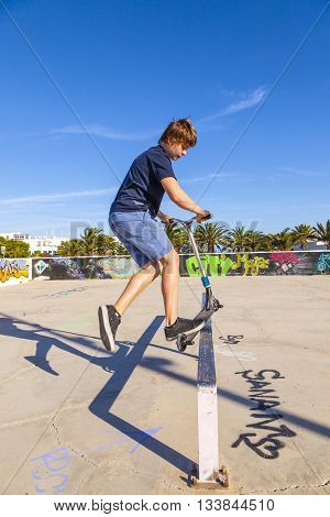 boy has fun jumping with his push scooter at the skate park