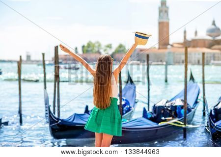 Young female traveler enjoying beautiful view on venetian chanal with gondolas and San Giorgio Maggiore island in Venice