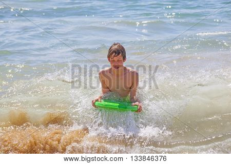cute boy enjoys surfing in the waves