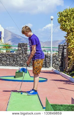 teenage boy loves to play outdoor Mini-Golf