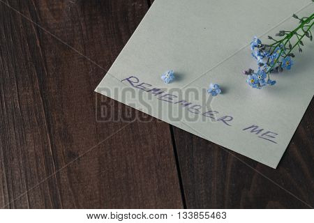 Forget-me-nots flowers on dark wooden background with paper