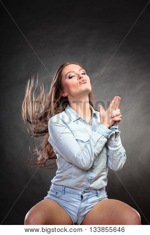 Woman Having Fun Pretending Hand Finger Is A Gun.