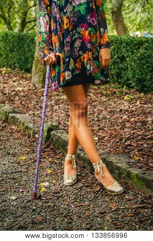 Young woman stands with walking stick on pebbled pathway
