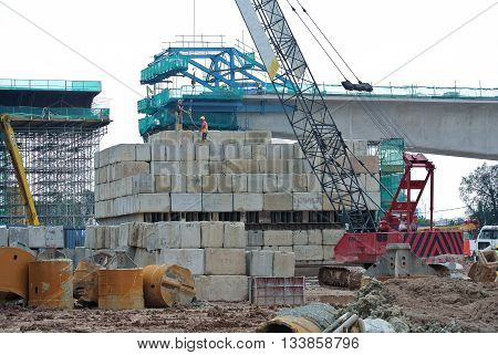 SELANGOR, MALAYSIA -FEBRUARY 11, 2015: Construction workers stacking the maintain load test block at the construction site in Selangor, Malaysia. The block used to test the piling integrity.