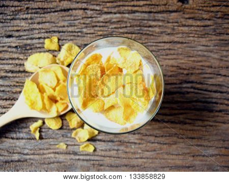 closeup top view milk with corn cerals in glass and corn cereals on wooden spoon.