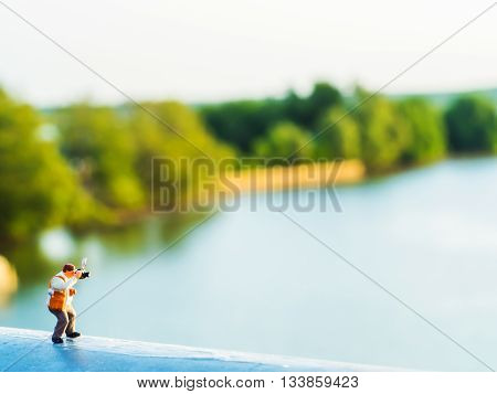 lovely plastic toy standing outdoor to take photos with riverside background