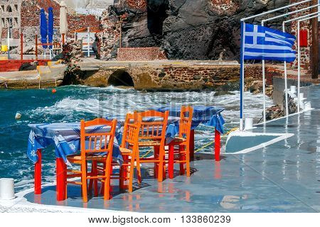 Cafe with the Greek flag on the shores of the old harbor in Oia. Greece. Santorini.