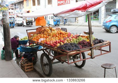 Cajamarca Peru - June 10 2016: Sleeping Andean woman sells fruit from bicycle street cart in Cajamarca Peru on June 10 2016