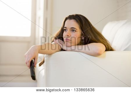 young beautiful woman lying at her apartment living room on sofa couch holding remote control watching television relaxed in girl enjoying TV movie focused and concentrated