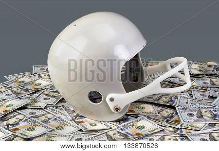 American football helmet on top stack of hundred dollar bills.