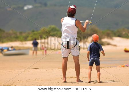 Kite Surfer On The Beach With A Boy
