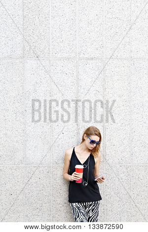 Portrait of young woman with coffee and cell phone in front of grey wall