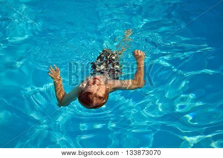 young hild enjoys swimming in the pool