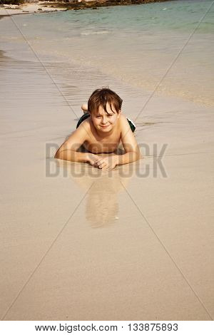 Boy Iy Lying At The Beach And Enjoying The Warmness Of The Water And Looking Self Confident And Happ