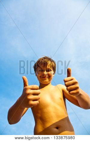 Happy Smiling Young Boy With Background Blue Sky Gives Fingersign