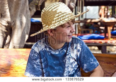 Boy Is Relaxing, Smiling And Happy And Has A Rest In The Sun At An Open Air Restaurant