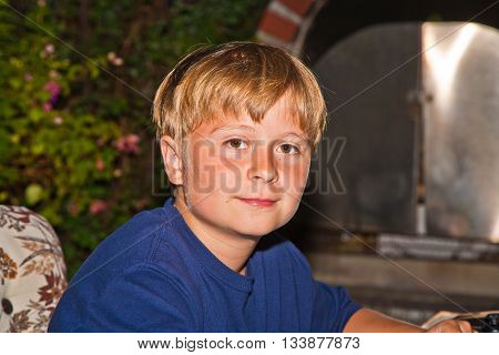 Boy Sitting At Night In The Garden
